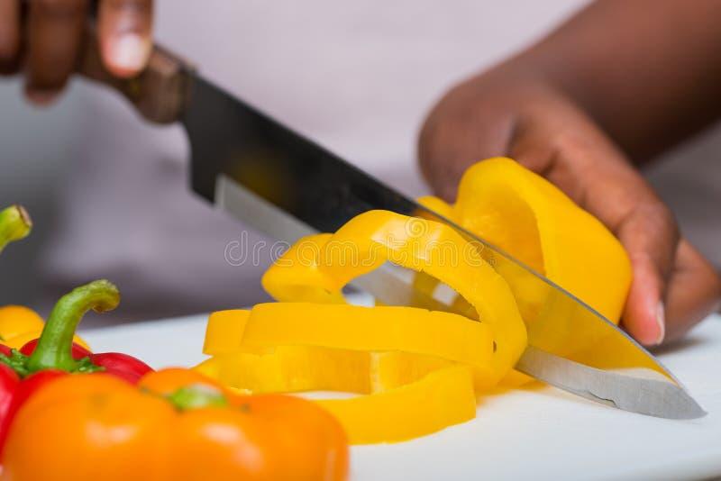 Handen die groene paprika's met mes, voedselvoorbereiding snijden stock foto