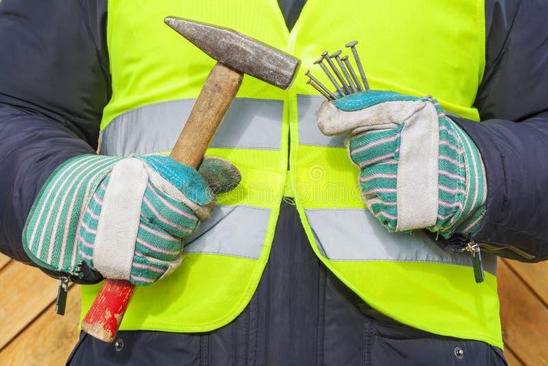 Handen die hamer en spijkers houden stock afbeelding