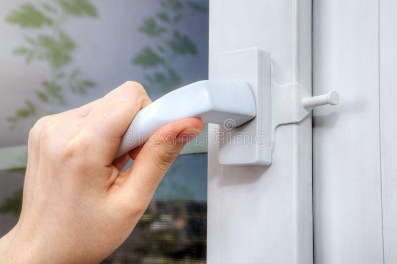 Handen die handvat draaien van plastic venster die waarop delimite openen stock foto