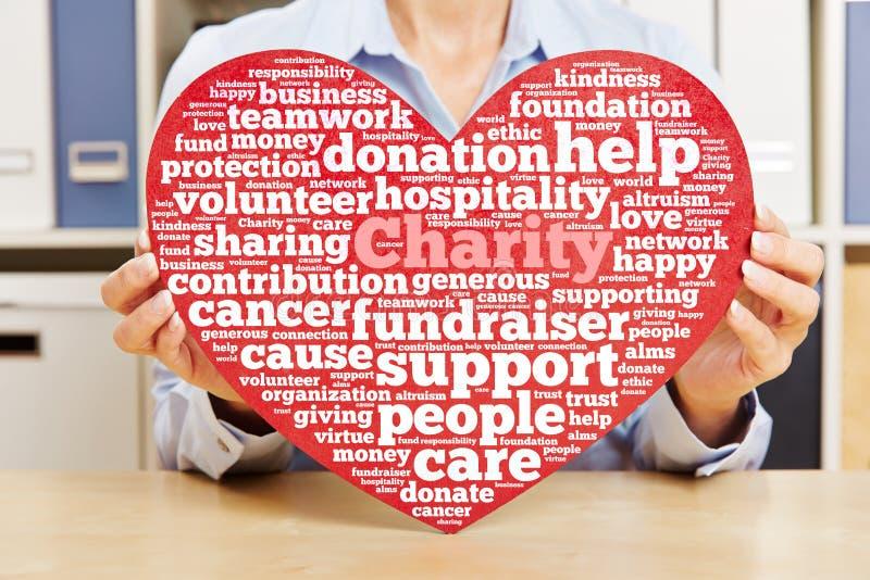 Handen die hart met de wolk van de liefdadigheidsmarkering houden stock afbeeldingen