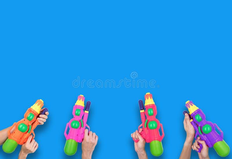 Handen die het stuk speelgoed van het kanonwater op blauwe achtergrond houden stock afbeelding