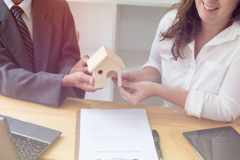 Handen die huismodel geven aan andere handen met overeenkomst over bureau royalty-vrije stock afbeeldingen
