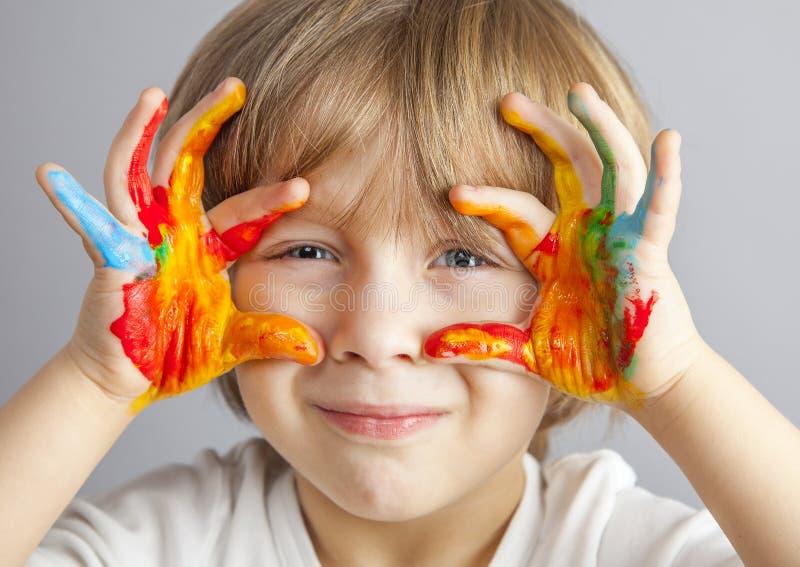 Handen die in kleurrijke verven worden geschilderd stock foto's