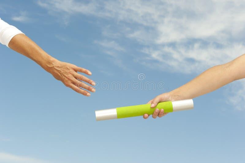 Handen die knuppel voor groepswerk bereiken stock foto's