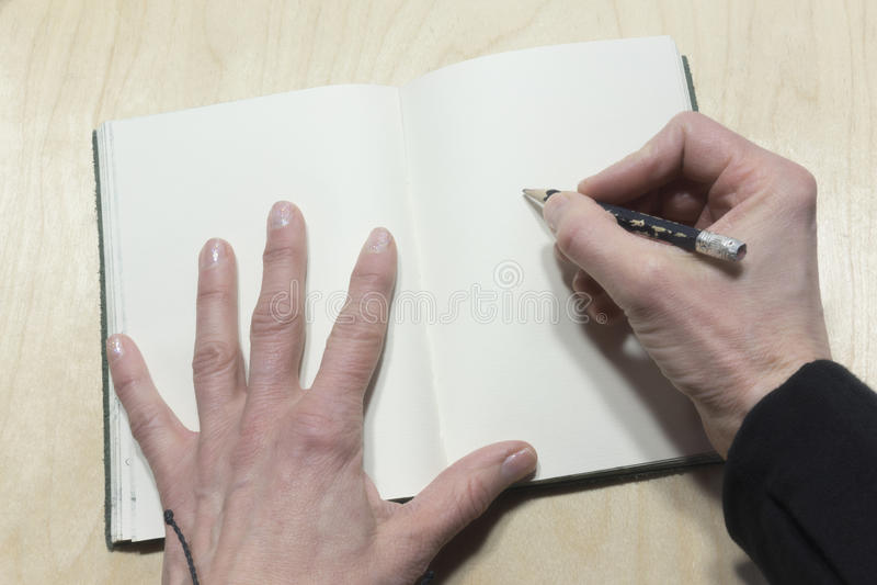 Handen die in leeg dagboek schrijven stock foto's