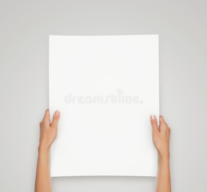 Handen die leeg die document blad houden op grijze achtergrond wordt geïsoleerd stock afbeelding