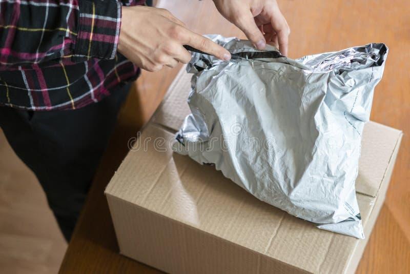 Handen die mes gebruiken om het geleverde pakket F thuis te openen royalty-vrije stock foto