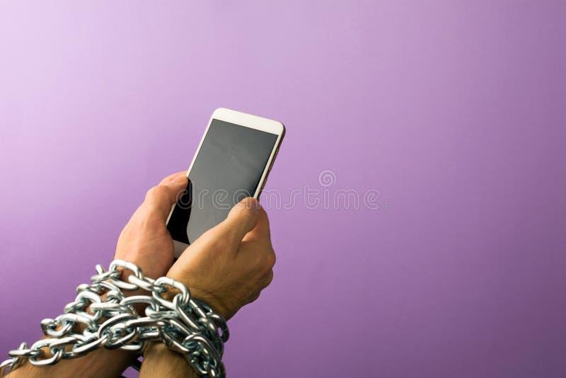 Handen die met metaalketting aan smartphone worden gebonden royalty-vrije stock fotografie