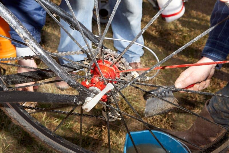 Handen die modderige fiets schoonmaken spokes stock fotografie