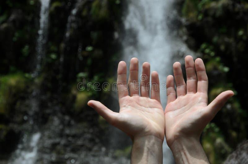 Handen die naar een waterval worden opgeheven stock fotografie