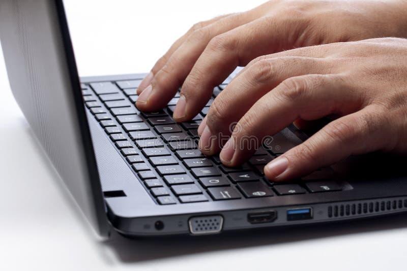 Handen die op Computerlaptop zijaanzicht typen stock foto's