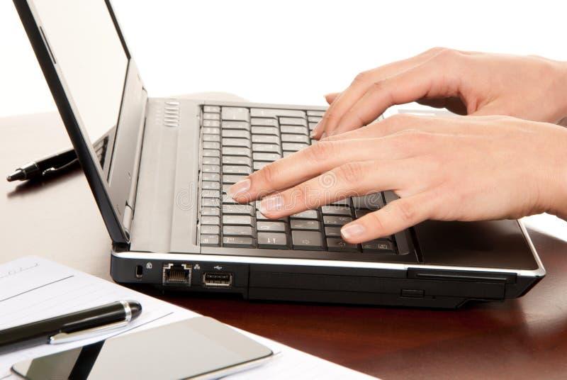 Handen die op laptop computertoetsenbord typen stock foto's