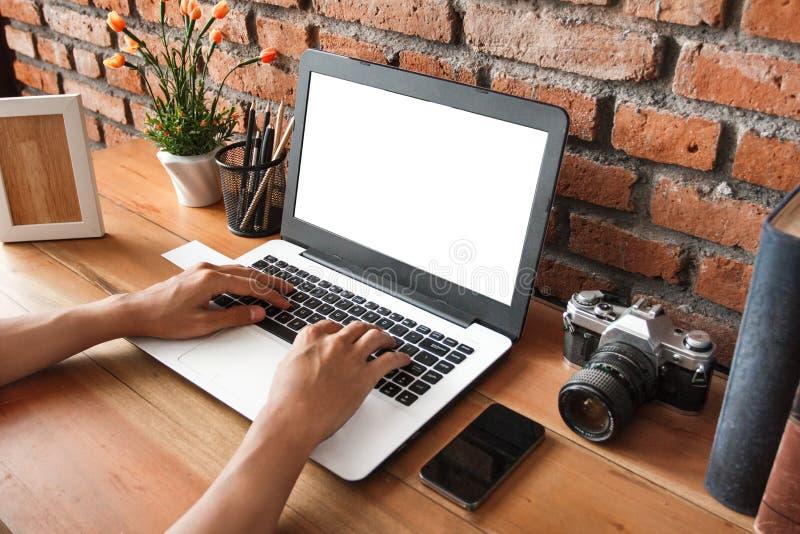 Handen die op laptop met houten lijst bij het werk ruimte typen stock afbeeldingen