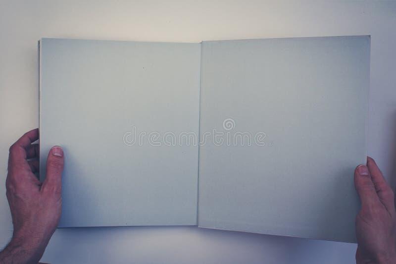 Handen die open boek met blanco pagina's houden stock afbeeldingen