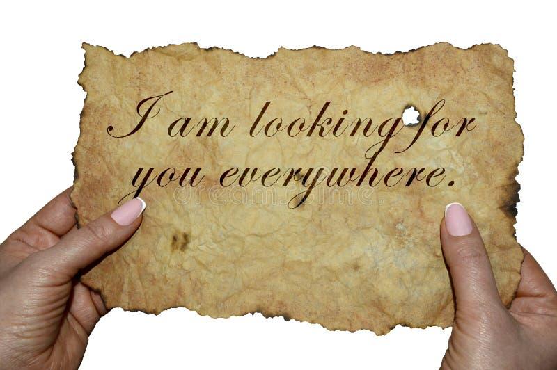 Handen die oud perkament met de woorden 'ik zoek u overal 'houden stock afbeeldingen