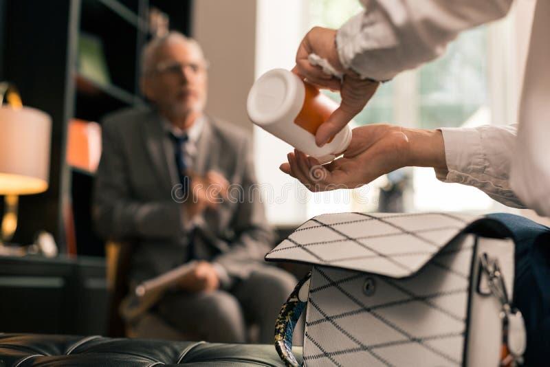 Handen die pillen nemen uit een pillendoos stock afbeeldingen