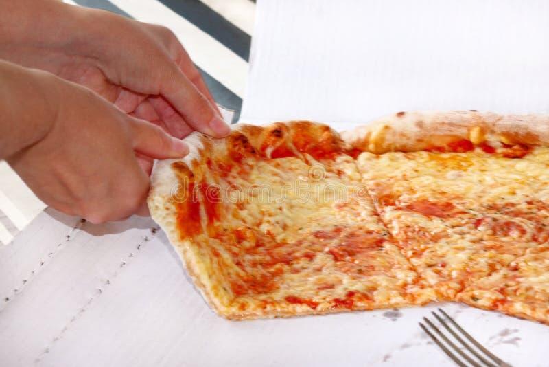 Handen die plakken van pizza Margarita nemen De hand op stukken van heerlijke pizza wordt getrokken die, sluit omhoog royalty-vrije stock fotografie
