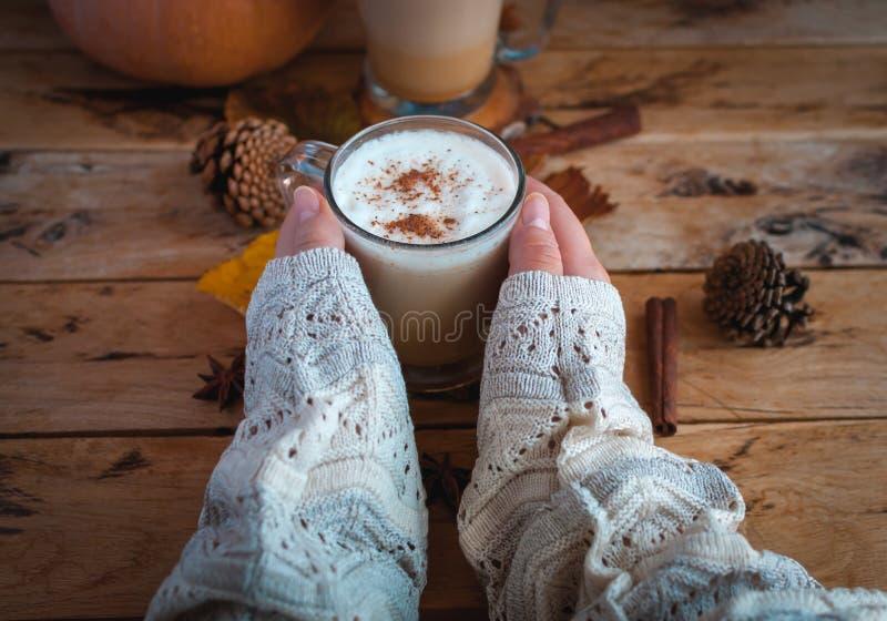 Handen die pompoenkruid latte in glaskop houden, op houten achtergrond royalty-vrije stock afbeelding