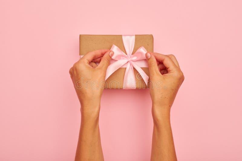 Handen die roze boog op een huidige doos binden royalty-vrije stock fotografie