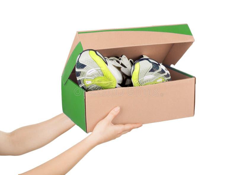 Handen die schoenen in een doos houden royalty-vrije stock fotografie