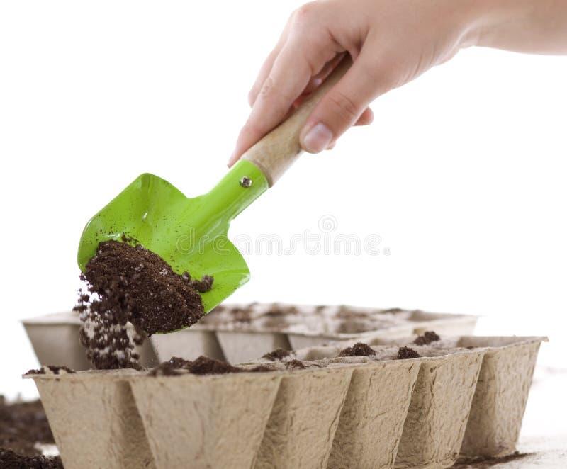 Handen die Schop met behulp van die Grond plaatst in de Potten van het Compost stock afbeelding
