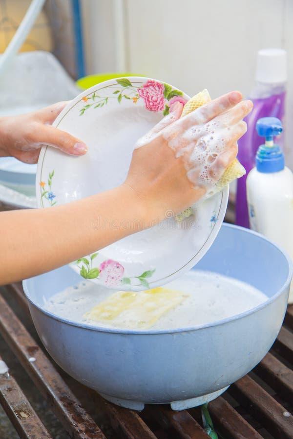 Handen die schotels met lopend water van tapkraan in gootsteen wassen royalty-vrije stock afbeeldingen
