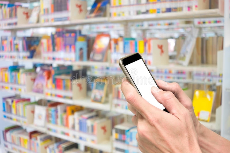 Handen die smartphone in bibliotheek gebruiken royalty-vrije stock afbeeldingen