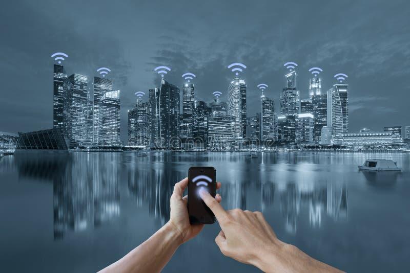Handen die smartphone en cityscape het concept van het wifinetwerk houden royalty-vrije stock foto