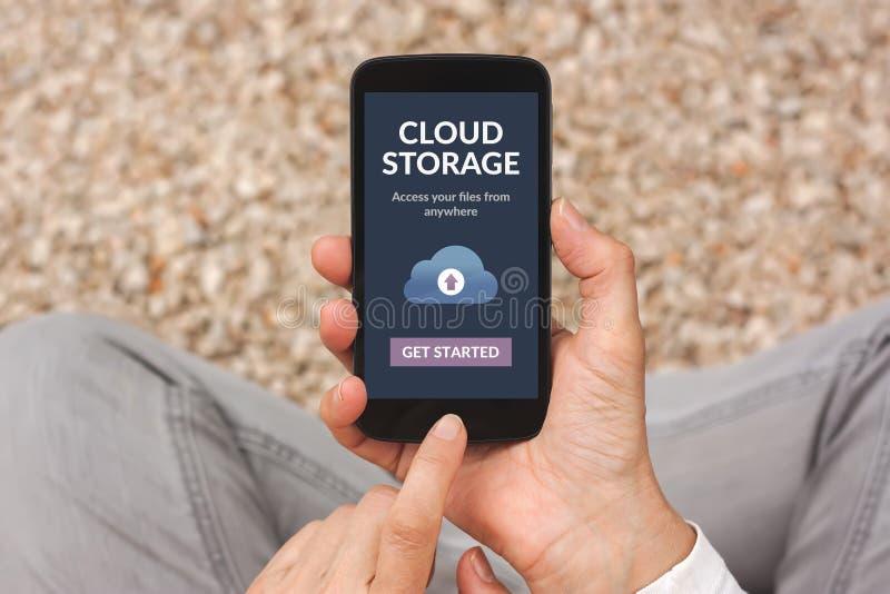 Handen die smartphone met app van de wolkenopslag concept op puinkegel houden royalty-vrije stock afbeelding