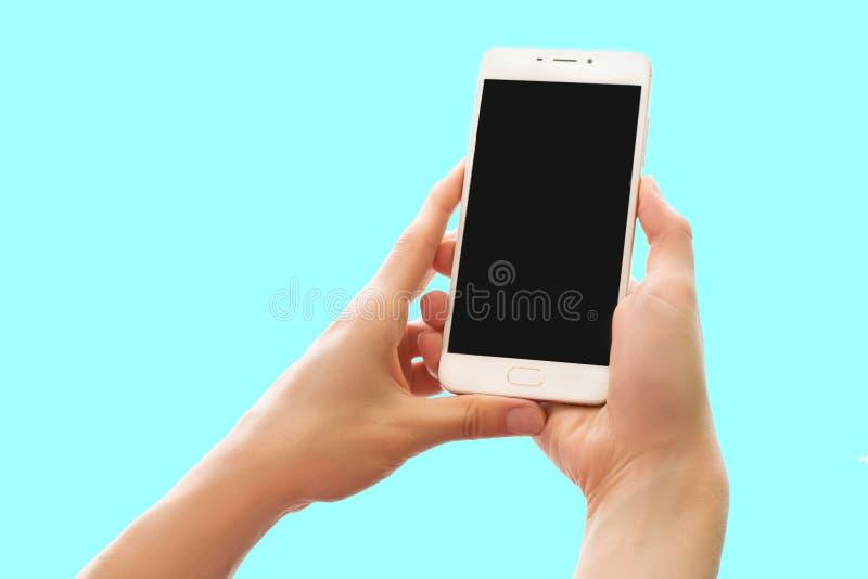 Handen die smartphone met het zwarte die scherm houden op pastelkleur blauwe achtergrond wordt geïsoleerd royalty-vrije stock foto's