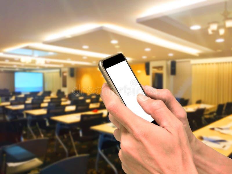 Handen die smartphone in vergaderzaal gebruiken stock afbeeldingen