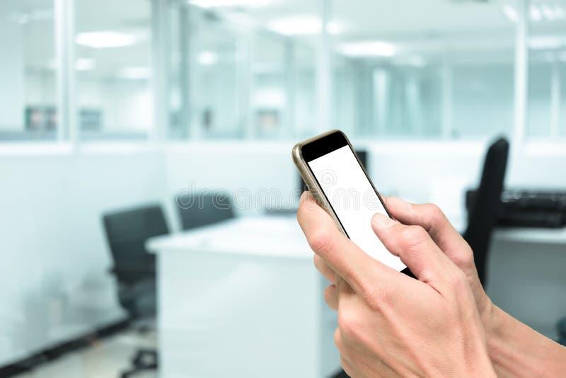 Handen die smartphone in werkend bureau gebruiken royalty-vrije stock afbeeldingen