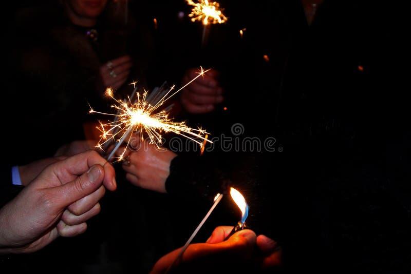 Handen die sterretjes houden De mensen staken de sterretjes onder de chiming klok voor het nieuwe jaar aan royalty-vrije stock afbeelding