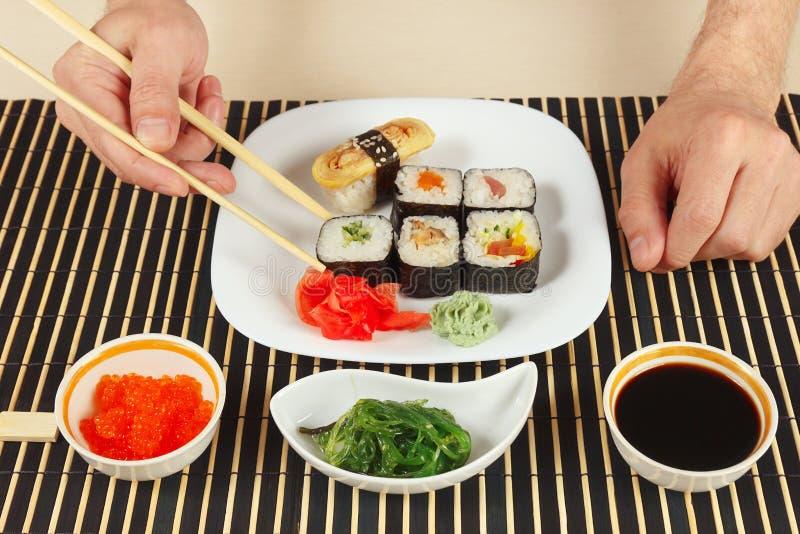 Handen die sushi met eetstokjes nemen Sushireeks, chukasalade, sojasaus en zalmkaviaar op zwarte bamboemat stock afbeeldingen
