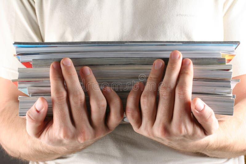 Handen die tijdschriften houden stock afbeeldingen