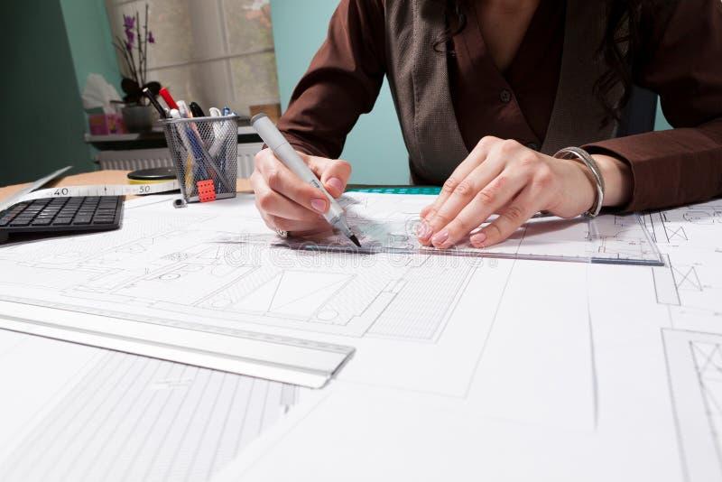 Handen die van architectenvrouw aan blauwdrukken werken royalty-vrije stock afbeelding
