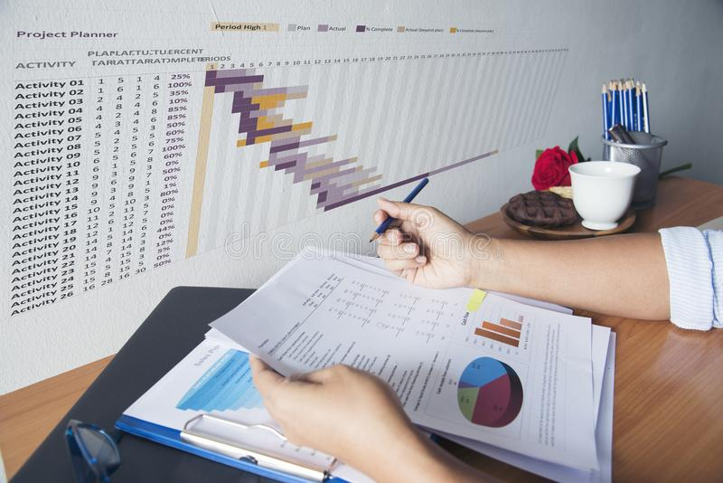Handen die van Bedrijfsvrouw aan haar bureau werken Lezingsgrafiek en grafiek royalty-vrije stock foto