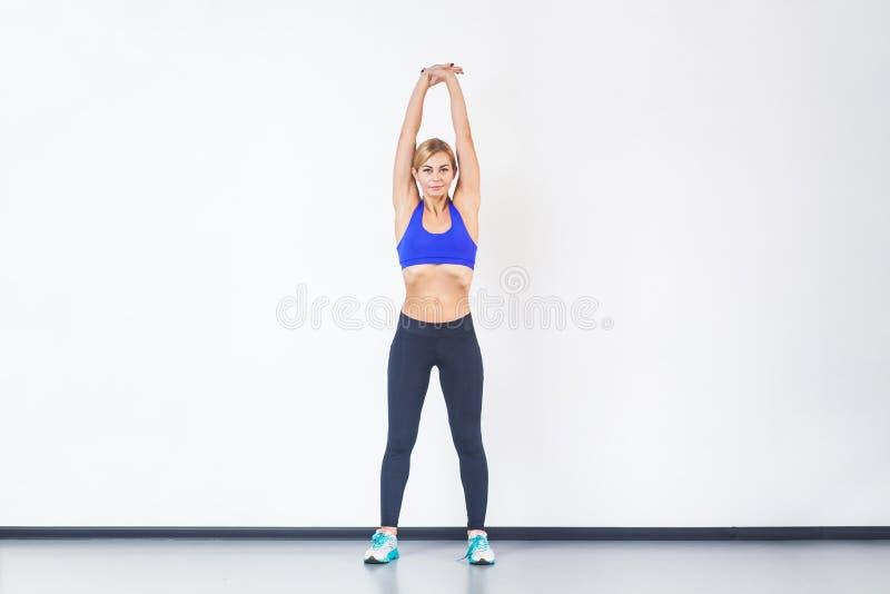Handen die van de blonde de atletische vrouw omhoog, geschiktheidsoefening doen stock fotografie