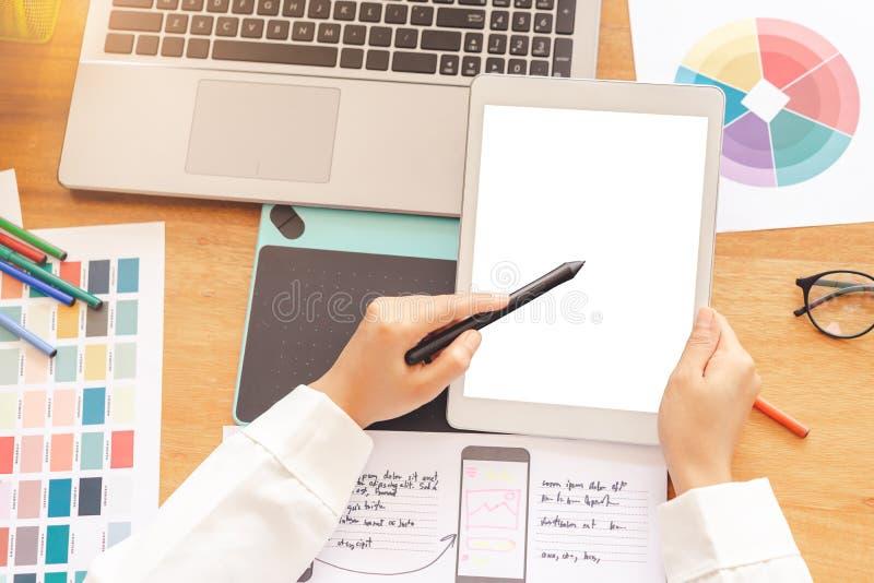 Handen die van de kunstenaars de creatieve ontwerper pentablet gebruiken die op het witte model van het schermsmartphone schetsen stock fotografie