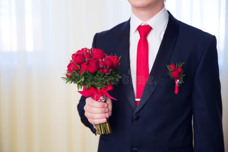 Handen die van huwelijksbruidegom klaar in kostuum worden De bruidegom houdt wij stock afbeelding