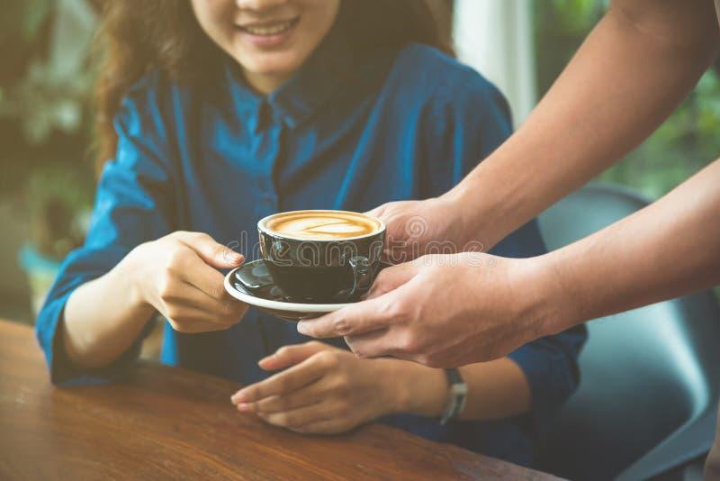 Handen die van kelner een kop van koffie dienen aan klant royalty-vrije stock afbeeldingen