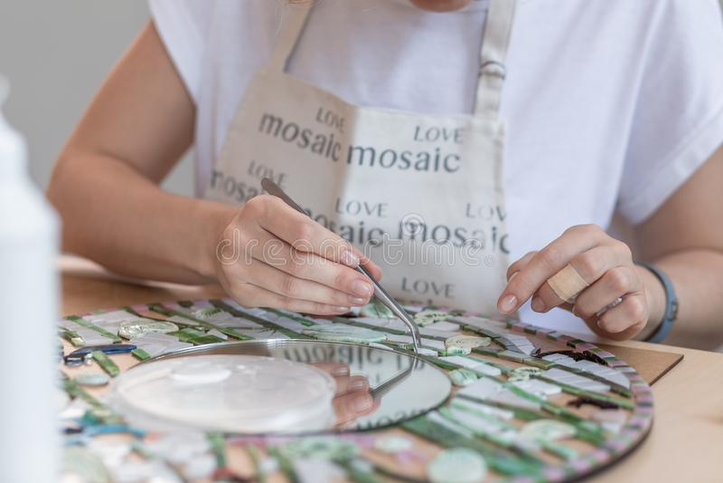 Handen die van meester aan nieuw modern kleurrijk mozaïek werken Close-up royalty-vrije stock foto