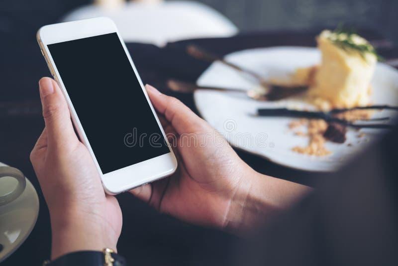 Handen die witte mobiele telefoon met het lege zwarte scherm met een plaat van cake op houten lijst in restaurant houden stock foto