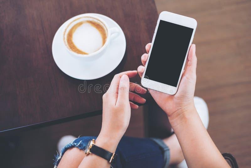 Handen die witte mobiele telefoon met het lege zwarte scherm met koffiekop houden op houten lijst en vloerachtergrond royalty-vrije stock foto