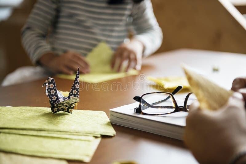 Handen die zwaanorigami op houten lijst maken stock afbeeldingen