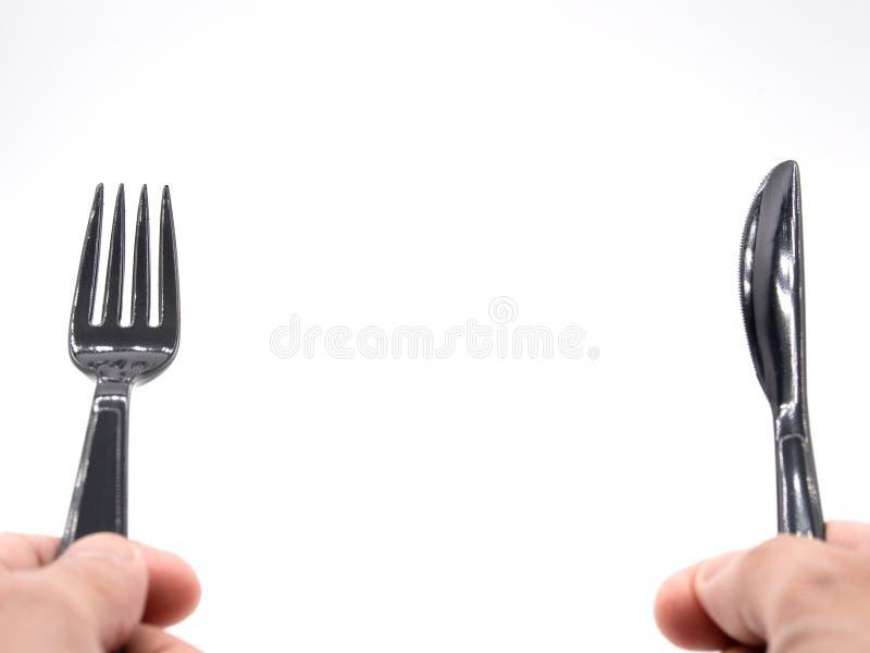 Handen die zwart plastic vork en mes houden stock foto's