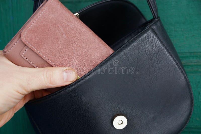 Handen drar ut en brun plånbok från en öppen svartläderpåse fotografering för bildbyråer