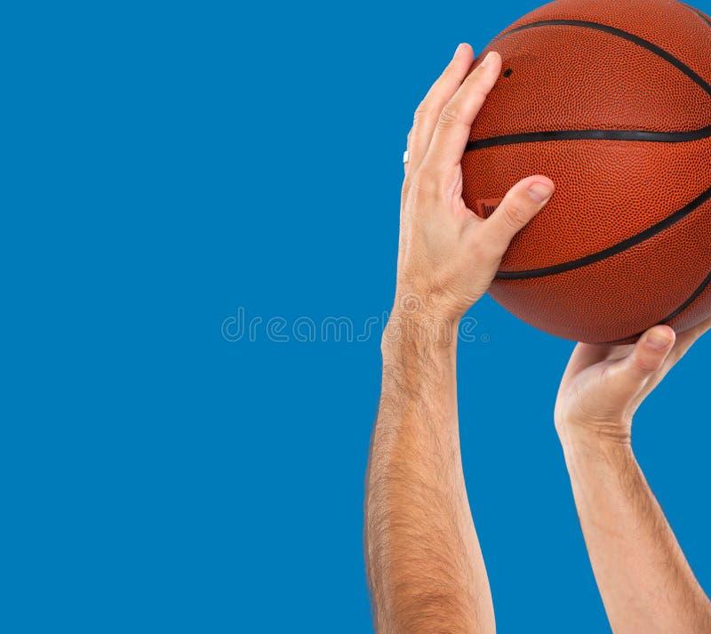 Handen en basketbal op een blauwe achtergrond royalty-vrije stock foto