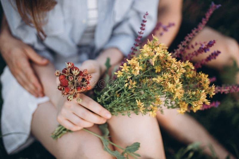 Handen en benen van de bloemen en de bessen van de paarholding royalty-vrije stock fotografie