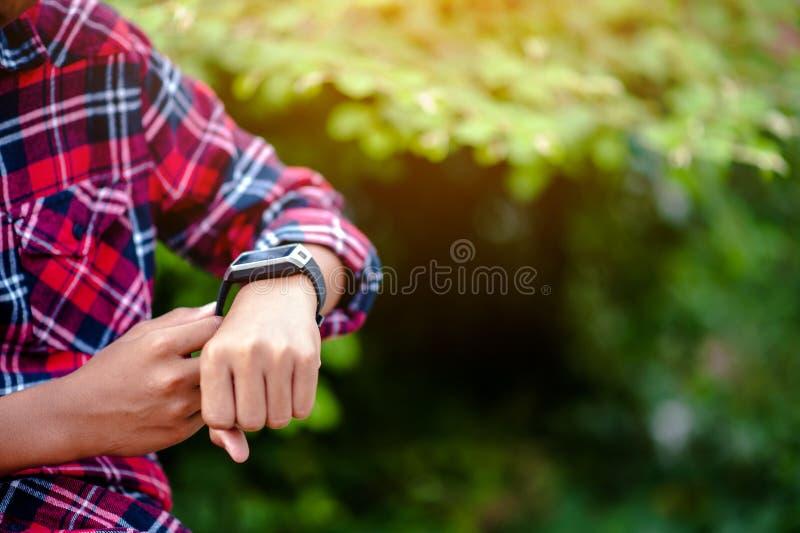Handen en digitale horloges van jongenshorloge de tijd in de pols T royalty-vrije stock afbeelding